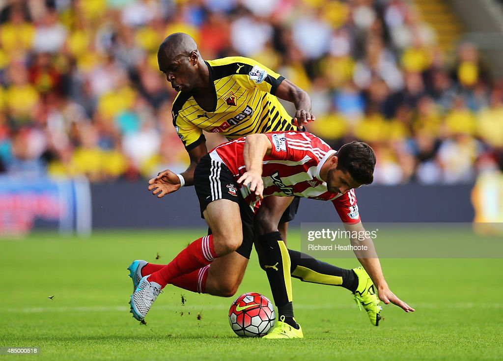 Shane Long of Southampton is challenged by Allan-Romeo Nyom of Watford during the Barclays Premier League match between Watford and Southampton at Vicarage Road on August 23, 2015 in Watford, England.