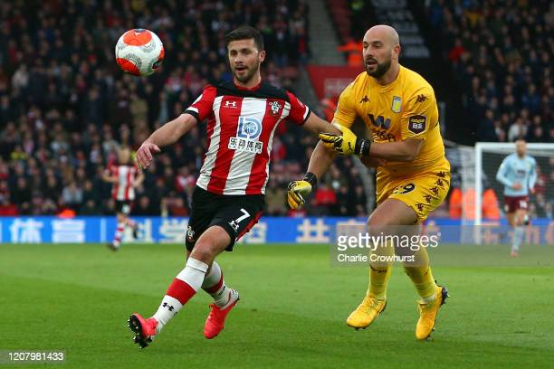 Shane Long of Southampton is challenged by Pepe Reina of Aston Villa during the Premier League match between Southampton FC and Aston Villa at St...