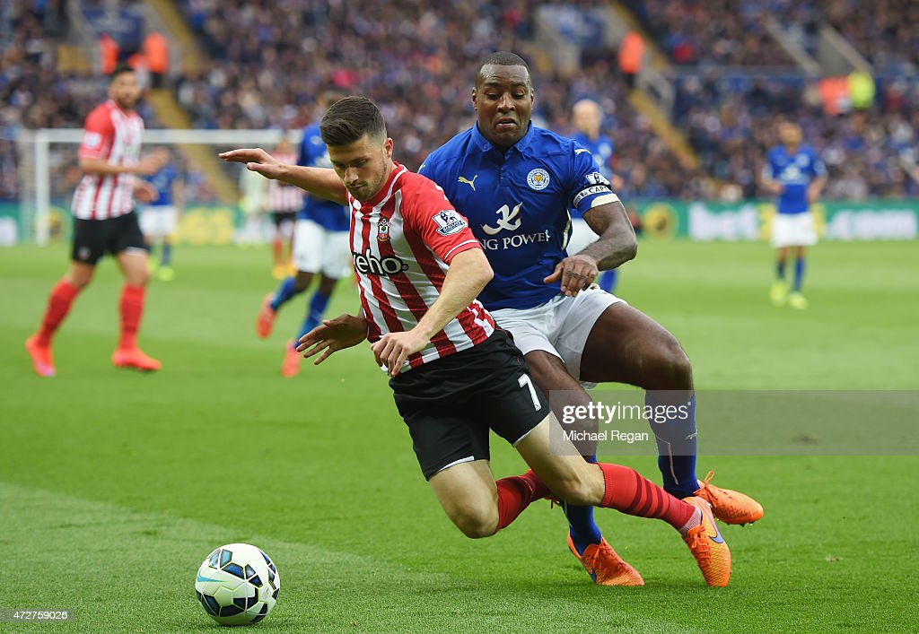 Shane Long of Southampton is challenged by Wes Morgan of Leicester City during the Barclays Premier League match between Leicester City and Southampton at The King Power Stadium on May 9, 2015 in Leicester, England.