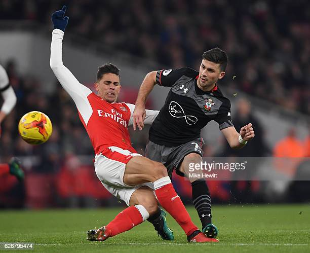 Shane Long of Southampton is tackled by Gabriel Paulista of Arsenal during the EFL Cup quarter final match between Arsenal and Southampton at the...