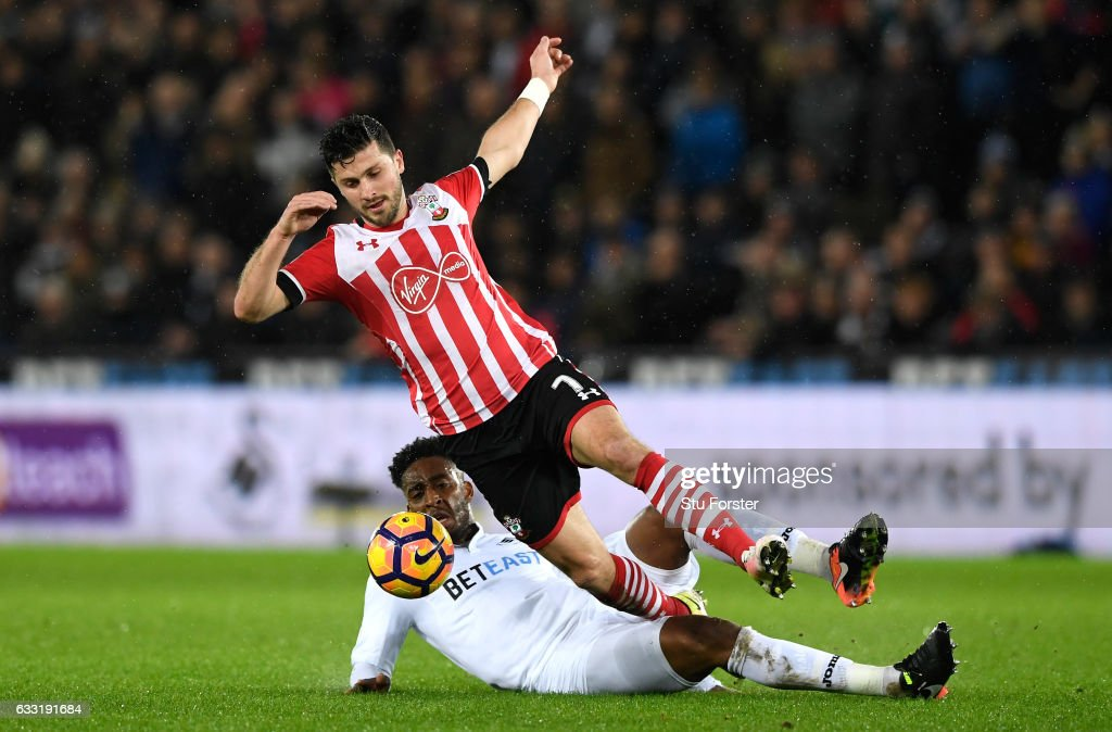 Shane Long of Southampton is tackled by Leroy Fer of Swansea City during the Premier League match between Swansea City and Southampton at Liberty Stadium on January 31, 2017 in Swansea, Wales.