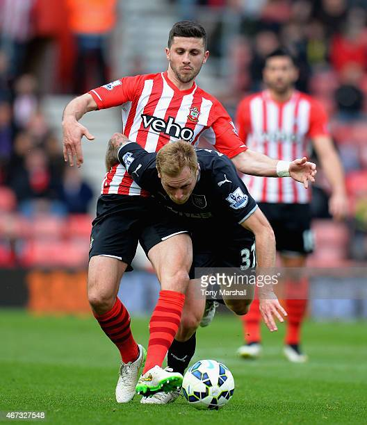 Shane Long of Southampton is tackled by Scott Arfield of Burnley during the Barclays Premier League match between Southampton and Burnley at St...