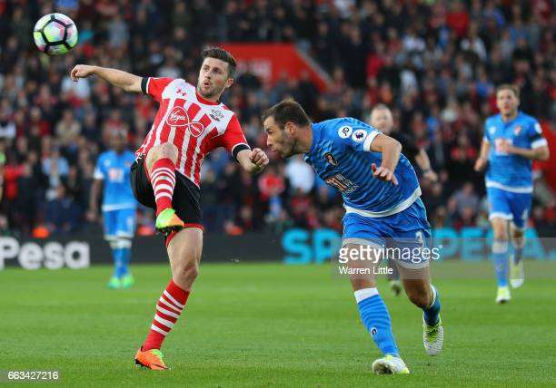 Shane Long of Southampton is tackled by Steve Cook of AFC Bournemouth during the Premier League match between Southampton and AFC Bournemouth at St...