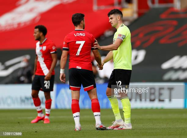 Shane Long of Southampton talks to John Egan of Sheffield United following the Premier League match between Southampton FC and Sheffield United at St...