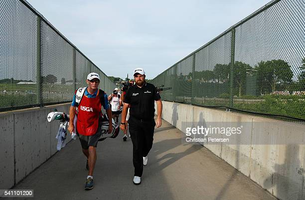 Shane Lowry of Ireland and caddie Dermot Byrne walk across the bridge over the Pennsylvania Turnpike during the third round of the US Open at Oakmont...