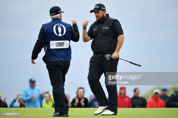 Shane Lowry of Ireland and his caddie Bo Martin react to his birdie on the 15th green during the final round of the 148th Open Championship held on...