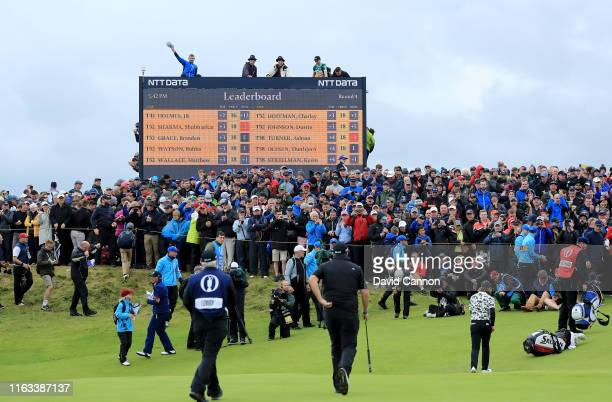 Shane Lowry of Ireland and Tommy Fleetwood of England leave the green on the 16th hole as spectators clamber for a view on the scoreboard during the...
