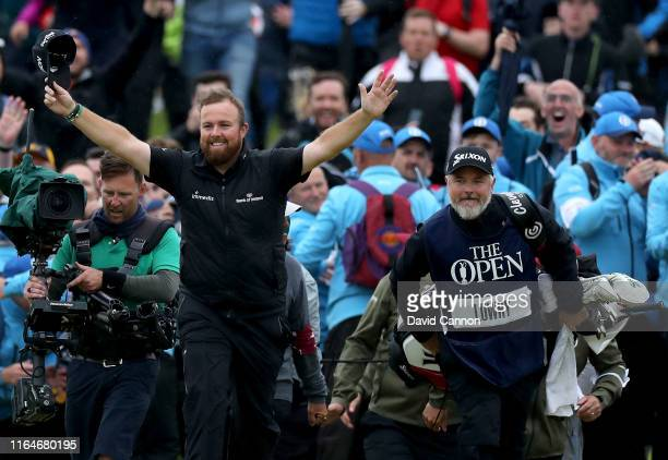 Shane Lowry of Ireland breaks through the huge crowds on the 18th hole and celebrates with his caddie Brian Martin on his way to completing his...