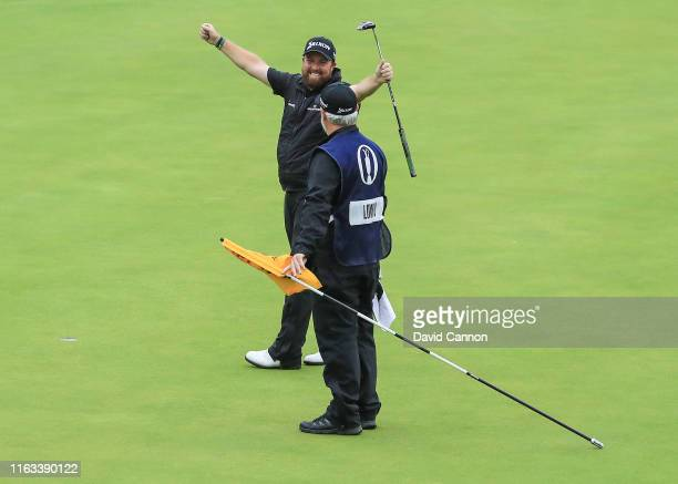 Shane Lowry of Ireland celebrates with his caddie Brian Martin after holing the final putt on the 18th hole on his way to completing his victory...