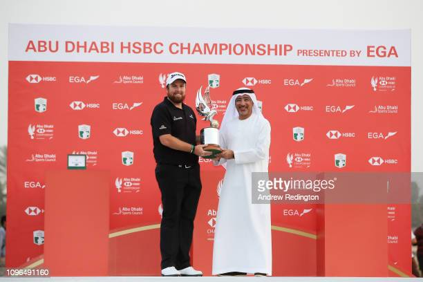 Shane Lowry of Ireland celebrates with the winner's trophy and Abdulfattah Sharaf , CEO of HSBC in the UAE, after Day Four of the Abu Dhabi HSBC Golf...