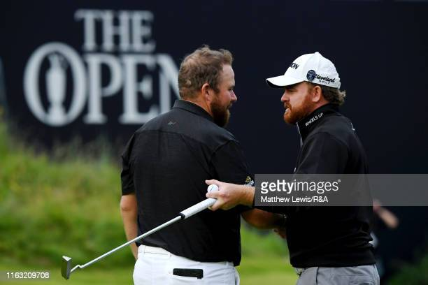 Shane Lowry of Ireland embraces JB Holmes of the United States following their third round of the 148th Open Championship held on the Dunluce Links...