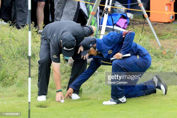 Shane Lowry of Ireland gets relief from a sprinkler head supervised by R&A Rules official David Bonsall on the 10th hole during the final round of...
