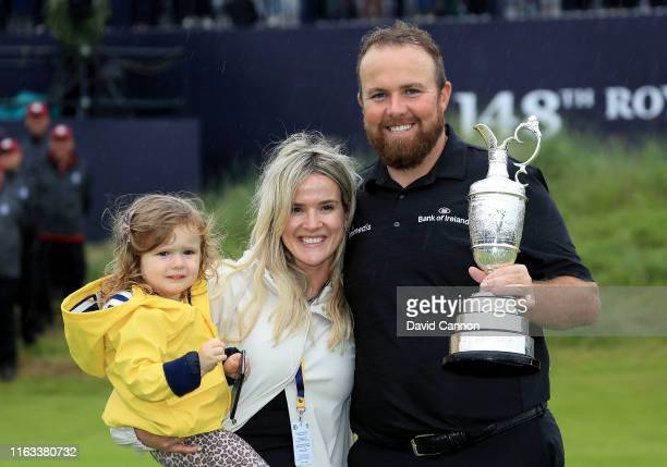 Shane Lowry of Ireland holds the Claret Jug with his wife Wendy Honner and their daughter Iris after his victory during the final round of the 148th...