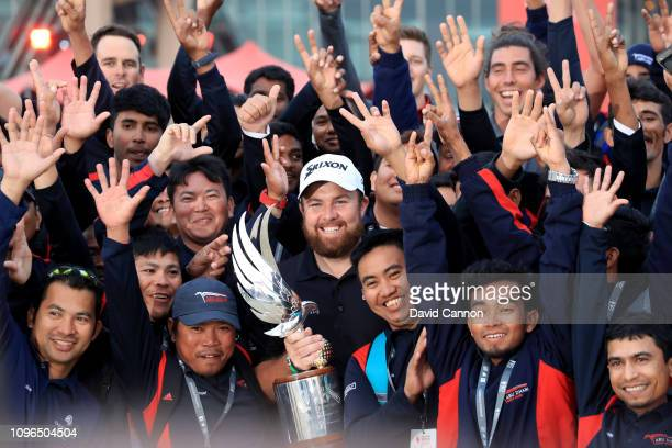 Shane Lowry of Ireland holds the trophy and members of teh Abu Dhabi Golf Club greens staff after his one shot win during the final round of the Abu...