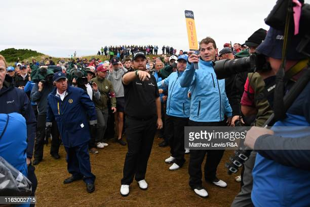 Shane Lowry of Ireland moves spectators after his tee shot on the 17th hole went wide during the second round of the 148th Open Championship held on...
