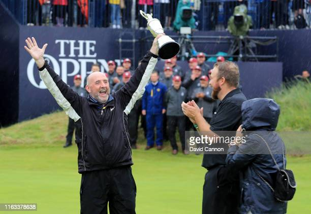Shane Lowry of Ireland passes the Claret Jug to his father Brendan Lowry as his mother Bridget Lowry watches on after their son's victory during the...