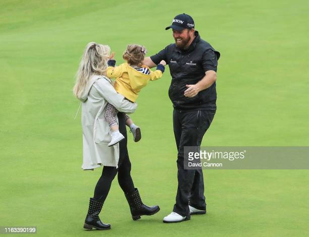 Shane Lowry of Ireland rushes to celebrate with his wife Wendy Honner and their daughter Iris after his victory during the final round of the 148th...