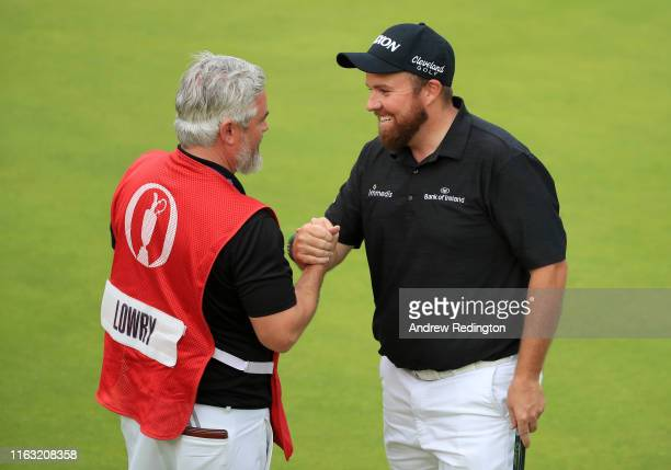 Shane Lowry of Ireland shakes hands with caddie Brian Martin on the 18th green during the third round of the 148th Open Championship held on the...