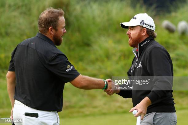 Shane Lowry of Ireland shakes hands with JB Holmes of the United States on the 18th green during the third round of the 148th Open Championship held...