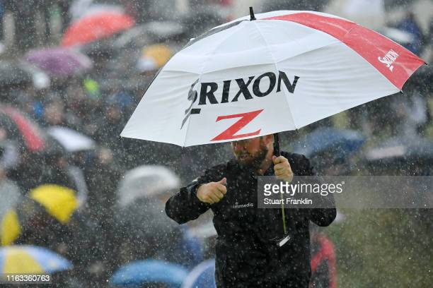 Shane Lowry of Ireland shelters from the rain on the eighth green during the final round of the 148th Open Championship held on the Dunluce Links at...