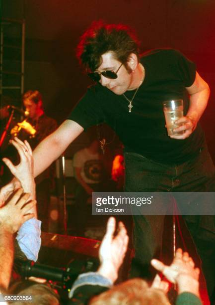 Shane MacGowan of The Pogues reaching out to the front rows of the crowd with one hand and holding a beer in the other while performing on stage at...