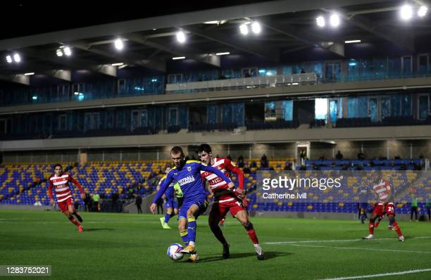 Shane McLoughlin of AFC Wimbledon is challenged by Danny Amos of Doncaster Rovers during the Sky Bet League One match between AFC Wimbledon and...