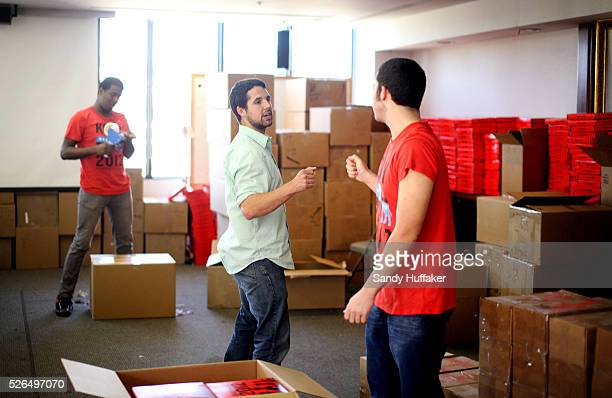 Shane McNeely, facing knuckle bumps Randy Stone while packing boxes of kits at the Invisible Childrens office in Sann Diego, CA on Thursday, March 8,...