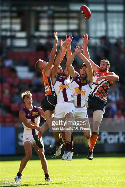 Shane Mumford and Adam Treloar of the Giants compete for a mark with Zac O'Brien of the Lions during the round 10 AFL match between the Greater...