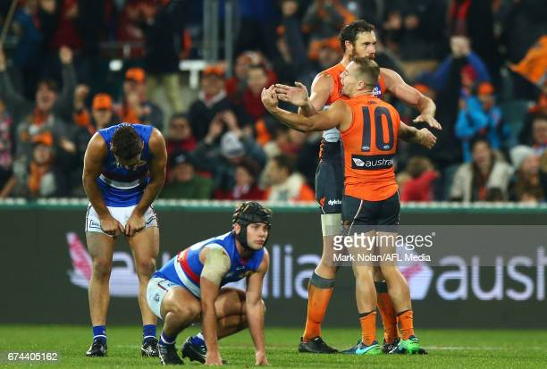 Shane Mumford and Devon Smith of the Giants celebrate winning the round six AFL match between the Greater Western Sydney Giants and the Western...