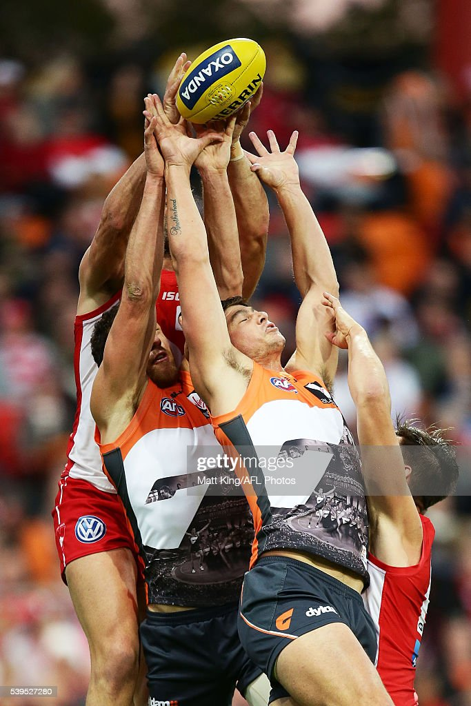 Shane Mumford of the Giants (L) and Jonathon Patton of the Giants (R) compete for the ball against Heath Grundy of the Swans (L) and Callum Sinclair of the Swans (R) during the round 12 AFL match between the Greater Western Sydney Giants and the Sydney Swans at Spotless Stadium on June 12, 2016 in Sydney, Australia.