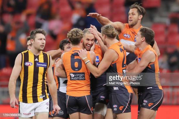 Shane Mumford of the Giants celebrates with team mates after kicking a goal during the round 5 AFL match between the Greater Western Sydney Giants...