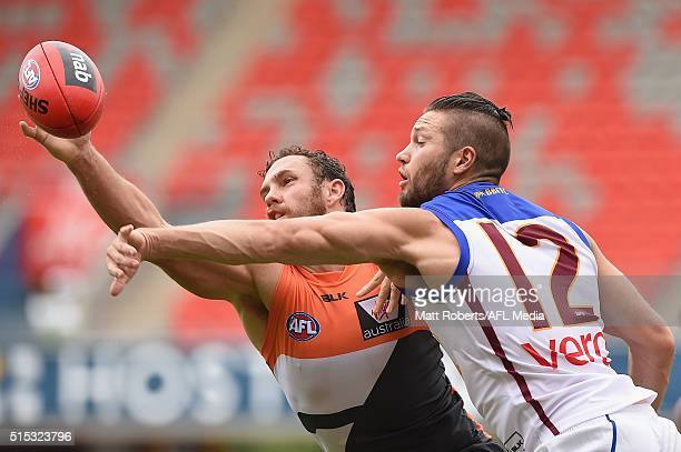Shane Mumford of the Giants competes for the ball against Stefan Martin of the Lion during the NAB Challenge AFL match between the Brisbane Lions and...
