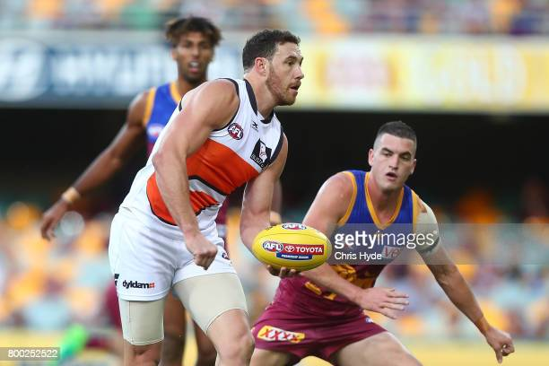 Shane Mumford of the Giants handballs during the round 14 AFL match between the Brisbane Lions and the Greater Western Sydney Giants at The Gabba on...