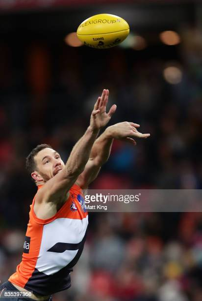 Shane Mumford of the Giants handles the ball during the round 22 AFL match between the Greater Western Sydney Giants and the West Coast Eagles at...