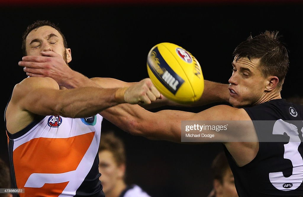Shane Mumford of the Giants is hit in the face by Cameron Wood of the Blues when competing for the ball during the round seven AFL match between the Carlton Blues and the Greater Western Sydney Giants at Etihad Stadium on May 16, 2015 in Melbourne, Australia.