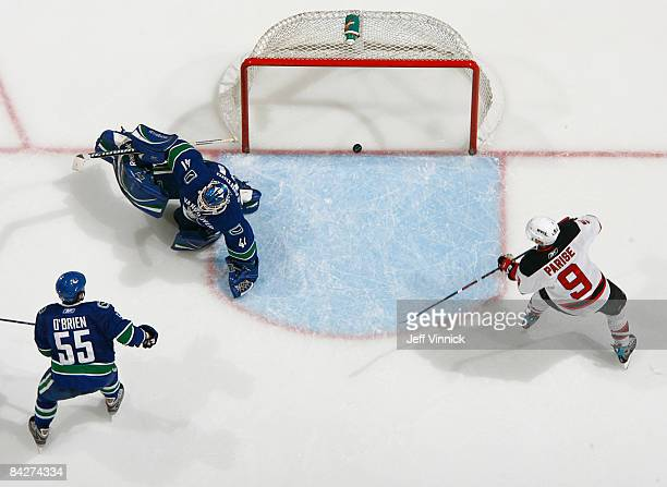 Shane O'Brien and Curtis Sanford of the Vancouver Canucks look on as Zach Parise of the New Jersey Devils scores during their game at General Motors...