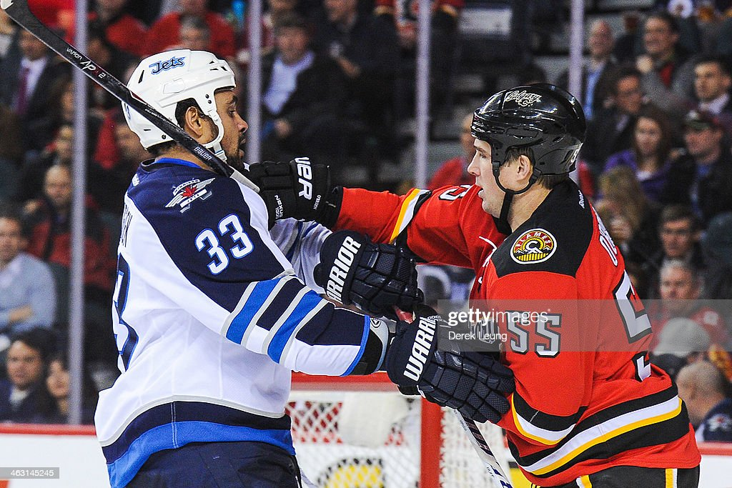 Shane O'Brien #55 of the Calgary Flames shoves Dustin Byfuglien #33 of the Winnipeg Jets during an NHL game at Scotiabank Saddledome on January 16, 2014 in Calgary, Alberta, Canada.