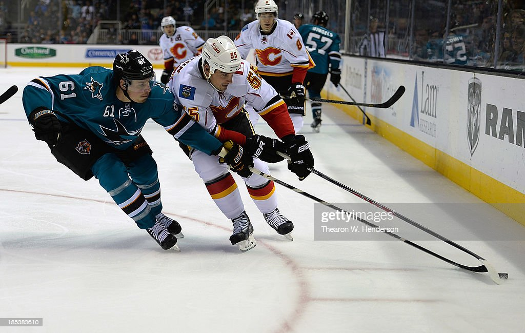 Shane O'Brien #55 of the Calgary Flames skates for control of the puck with Justin Braun #61 of the San Jose Sharks during the third period at SAP Center on October 19, 2013 in San Jose, California.