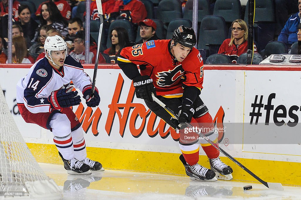 Shane O'Brien #55 of the Calgary Flames skates with the puck past Blake Comeau #14 of the Columbus Blue Jackets during an NHL game at Scotiabank Saddledome on November 20, 2013 in Calgary, Alberta, Canada.