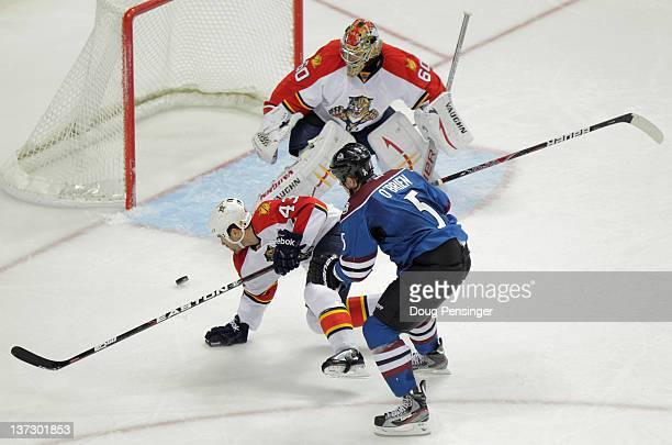 Shane O'Brien of the Colorado Avalanche takes a shot against Mike Weaver of the Florida Panthers and goalie Jose Theodore of the Florida Panthers at...