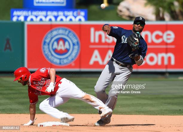 Shane Robinson of the Los Angeles Angels of Anaheim is safe at second as Robinson Cano of the Seattle Mariners throws to first but is unable to make...