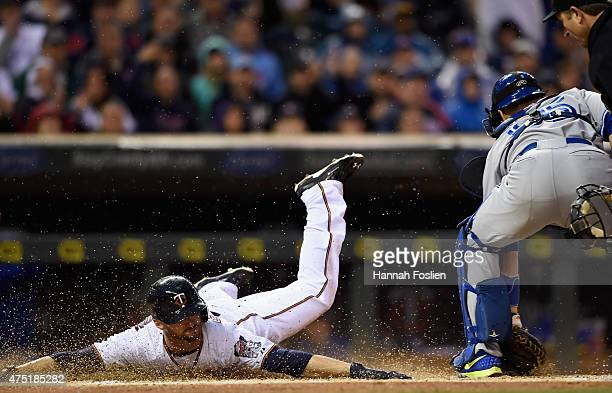 Shane Robinson of the Minnesota Twins slides safely past Russell Martin of the Toronto Blue Jays at home plate to score a run during the first inning...