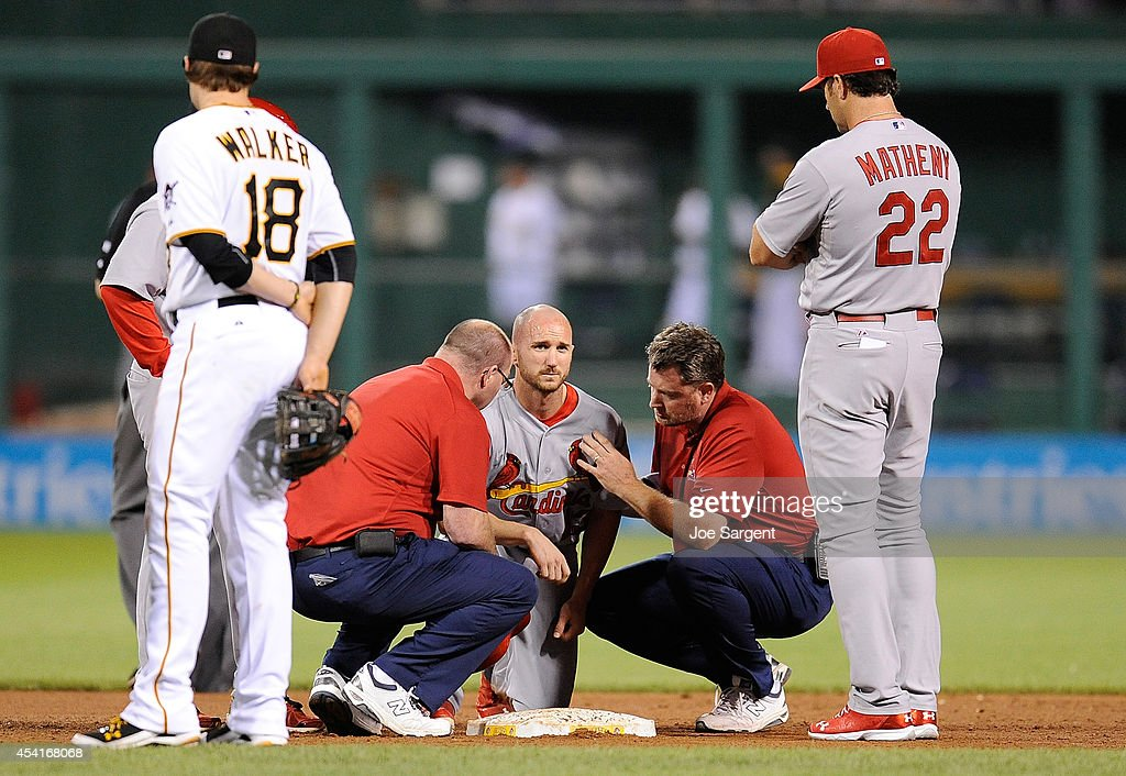 Shane Robinson #43 of the St. Louis Cardinals is looked at by trainers after being injured on a steal attempt during the ninth inning against the Pittsburgh Pirates on August 25, 2014 at PNC Park in Pittsburgh, Pennsylvania.