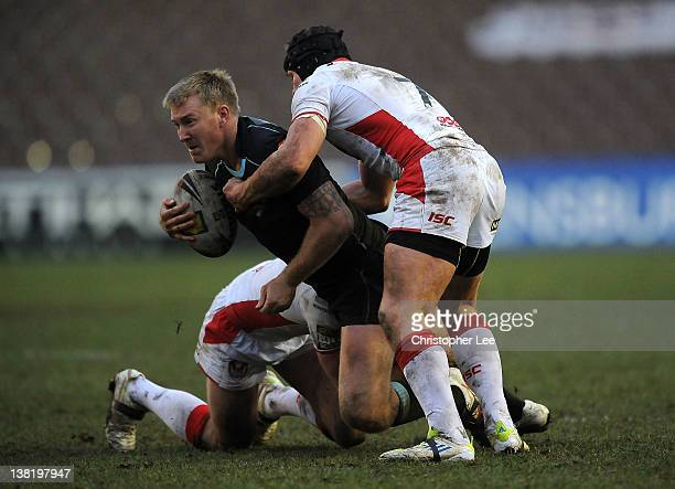 Shane Rodney of Broncos is tackled by James Roby and Jonny Lomax of St Helens during the Stobart Super League match between London Broncos and St...