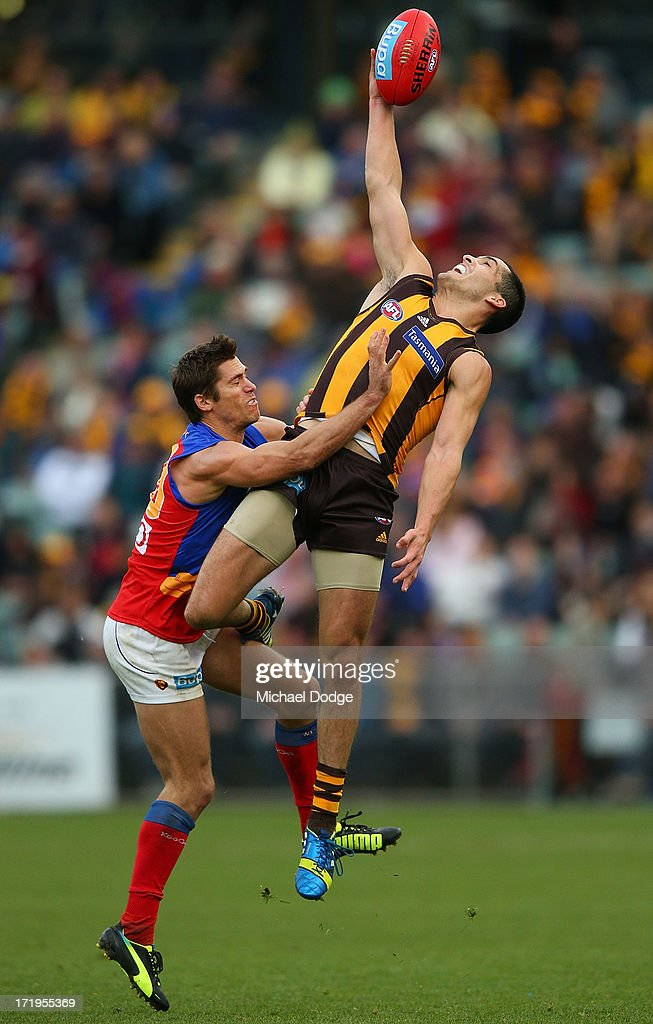 Shane Savage (L) of the Hawks contests for the ball against Simon Black of the Lions during the round 14 AFL match between the Hawthorn Hawks and the Brisbane Lions at Aurora Stadium on June 30, 2013 in Launceston, Australia.