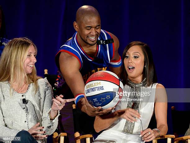 Shane 'Scooter' Christensen from the Harlem Globetrotters gives the basket ball to cast member Cheryl Burke as executive producer Audrey Morrissey...