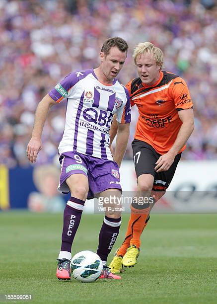 Shane Smeltz of the Glory fends off Mitchell Nichols of the Roar during the round one ALeague match between the Perth Glory and the Brisbane Roar at...