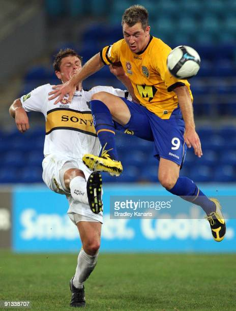 Shane Smeltz of United and Ben Sigmund of the Phoenix compete for the ball during the round nine A-League match between Gold Coast United and the...