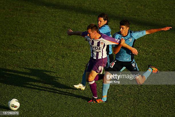Shane Smetlz of the Glory is challenged by Karol Kisel and Terry Antonis of Sydney FC during the round nine A-League match between Sydney FC and...