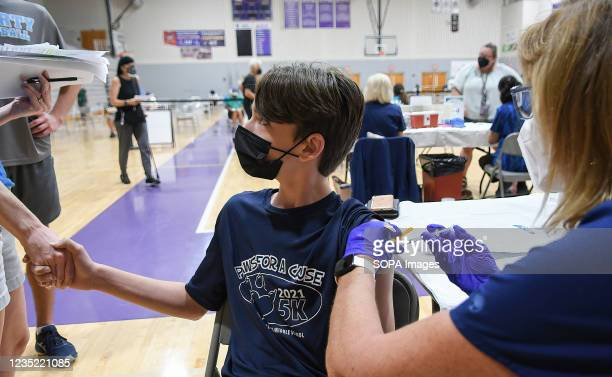 Shane Tebbens, age 12, holds his motherís hand while a nurse gives him a shot of the Pfizer COVID-19 vaccine at a vaccination clinic at Winter...